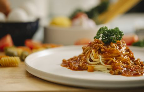 Appetizing spaghetti pasta with bolognese sauce served in kitchen