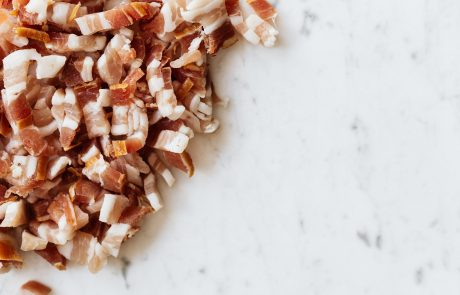 Heap of sliced bacon on marble surface